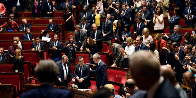 French members of Parliament applaud French Minister of Public Action and Accounts Gerald Darmanin (C) after a winning vote on public finance programming for 2018 - 2022 on October 24, 2017, at the French National Assembly in Paris. / AFP PHOTO / Eric FEFERBERG